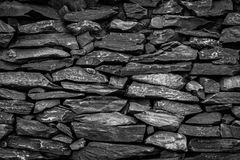 Pattern gray color of modern style design. Decorative uneven cracked real stone wall surface with cement black Royalty Free Stock Photos
