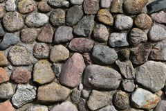 Stones outdoors wall background. Pattern of grey decorative random sized stones outdoors wall with concrete connection as natural surface background stock images