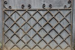 The pattern and grid of steel rods on a gray metal wall. Texture of the grating of steel rods on a gray metal wall Stock Photo