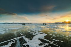 Pattern on ice of lake Baikal during sunset with two cars. Siberia Russia. Transparent ice of Lake Baikal is cut by fancy crack patterns powdered with light snow royalty free stock image