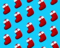 Pattern made with Christmas Red Socks on Blue Background. Creative Minimal Holiday Composition. Flat Lay stock images