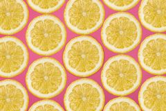 Pattern made from fresh lemon slices on a pink background, overhead view, flatlay. Fruit background. Pattern made from fresh lemon slices on a pink background royalty free stock image