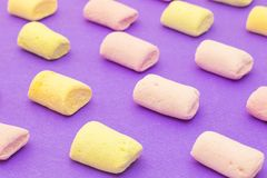 Pattern with marshmallows on violet background. Pattern with yellow and purple yummy marshmallows on violet background royalty free stock photography
