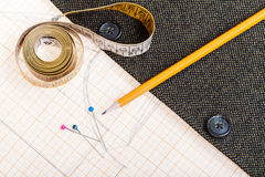 Pattern, measure tape, pencil, pins, jacket. Dressmaking still life - top view of cutting table with pattern, measure tape, pencil, pins, tweed jacket Stock Photo