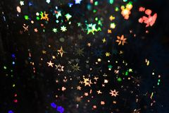 Pattern with multicolored stars on black textured holographic paper. royalty free stock photo