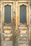 Pattern of old wooden double door with glass panes outside exposed to the weather. Close-up.  stock photos