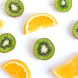 Pattern with oranges and kiwi slices on a white wooden background. The basis for the booklet, the background for the banner. Basis royalty free stock photos