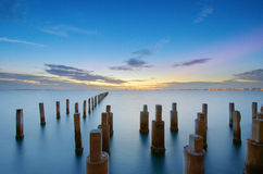 Pattern pillars in the sea on sunset time. Royalty Free Stock Images