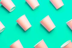 Pattern from Pink Paper Drinking Cups Arranged Diagonally on Light Green Turquoise Backgrounds. Birthday Party Celebration. Abstract Fashion Baby Shower Concept royalty free stock image