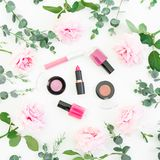 Pattern of pink rose flowers with eucalyptus and cosmetic: lipstick, shadows, mascara on white background. Flat lay, top view royalty free stock photography