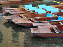 Pattern of punts moored on Cambridge canal. Pattern of wet wooden punts moored on canal in Cambridge on wet day royalty free stock photography