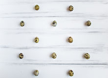 Pattern with quail eggs on white wooden vintage table. Flat lay, top view stock photos