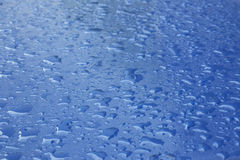 Pattern of raindrops on blue surface Royalty Free Stock Images
