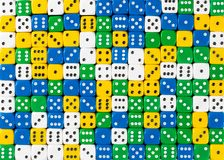 Pattern of random ordered white, yellow, green and blue dices royalty free stock image