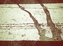 The pattern on the red background processes. The pattern on the ground caused by the old paint and weather Stock Photography