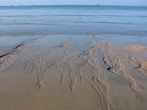 Large ebb on sea. Patterns on the sand after flowing water. Islands and ships on horizon Stock Photo