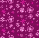 The pattern is seamless from beautiful, Christmas, carved, New Year`s, festive unique pink and purple snowflakes of different sha. Pes and sizes on a purple Royalty Free Stock Image