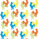 The pattern of silhouettes of roosters. Seamless ornamental pattern composed of silhouettes of colorful roosters on a light background Royalty Free Stock Photo
