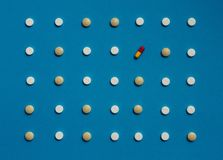 Pattern With Tablets And One Colored Pill On Blue Background, Top View. Medicine Healthcare Pharmacy Concept Stock Photos