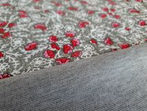 Vintage floral fabric with small red flowers on the grey background stock image