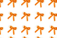 Pattern of turmeric silk gift bows isolated on white. Pattern of turmeric silk gift bows isolated on white background. Festive concept stock photos