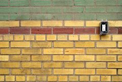 Pattern wall of coloured bricks with electrical outlet Royalty Free Stock Images