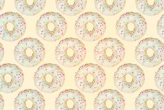 Pattern of a white donuts on a yellow background. Flat lay stock photography