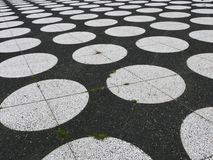 Spots of black and white. A pattern of white round spots on the black pavement Royalty Free Stock Photos