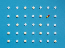 Pattern with white tablets and one Colored Pill On Blue Background. Medicine Healthcare Pharmacy Concept Stock Images