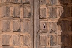 Pattern of wooden decorated ancient door with lock. Old wooden door and metal lock of facade exterior of church from thirteenth century, in Santa Maria de Riaza Stock Photos