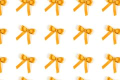 Pattern of yellow silk gift bows isolated on white. Pattern of yellow silk gift bows isolated on white background. Festive concept stock photos
