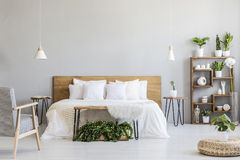 Free Patterned Armchair Near White Wooden Bed In Grey Bedroom Interior With Pouf And Plants. Real Photo Royalty Free Stock Image - 124693896