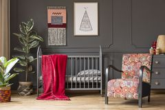 Free Patterned Armchair Next To Baby`s Bed With Red Blanket In Grey B Royalty Free Stock Photos - 126408928