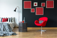 Patterned blanket on king-size bed. In stylish room with red chair and red pictures on black wall Royalty Free Stock Photos