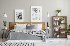 Patterned blanket on wooden bed between tables with plants in bedroom interior with posters. Real photo. Concept royalty free stock photo