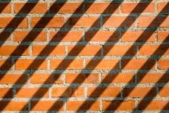 Patterned brick wall brown and has long shadows Stock Images