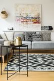 Patterned carpet and cushions on grey sofa in modern living room. Interior with painting. Real photo royalty free stock image
