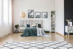 Posters in contrast bedroom interior. Patterned carpet near white cupboard in contrast bedroom interior with gallery of posters above bed Royalty Free Stock Photography