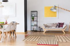 Multifunctional spacious room with sofa. Patterned carpet on wooden floor in multifunctional spacious room with sofa and dining table stock image