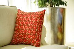 Patterned cushion. Red patterned cushion on couch Royalty Free Stock Images