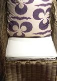 Patterned Cushion on Wicker Chair. Stylish and Bold Patterned Cushion on Elegant Rattan Chair stock image