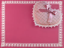 Patterned heart on pink with a lacy border Stock Photo