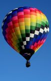 Patterned Hot Air Balloon. A very colorful hot air balloon soars in a clear blue sky Stock Photography