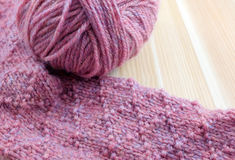 Patterned knitting with ball of pink yarn Stock Photos