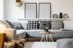 Patterned pillows on grey corner sofa in apartment. Interior with posters and pouf. Real photo royalty free stock photo