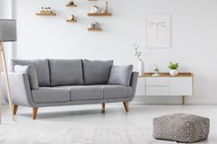 Patterned pouf and grey couch in minimal living room interior wi