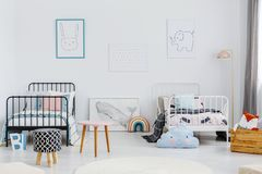Patterned stool in spacious children bedroom interior with posters above white and black bed. Real photo stock photo