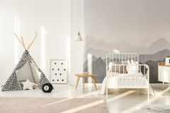 Teepee in kids room. Patterned teepee standing in bright kids room interior with white bed, mountain wallpaper and powder pink carpet royalty free stock images