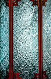 Patterned, texture blue glass in 3 pieces of glass, lit from behind, seperated by ornate copper coloured metal strips. Patterned, textured blue glass in three stock images