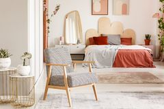 Patterned wooden armchair next to gold table in orange bedroom i Stock Photography